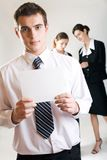 Businessman with blank note-card and two businesswomen. Young businessman with blank note-card and two businesswomen Stock Photos