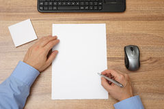 Businessman with blank paper and pen in hand to begin with wri. Ting. top view stock photo