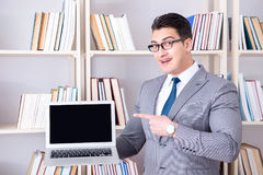 The businessman with a blank screen laptop working in the library. Businessman with a blank screen laptop working in the library Royalty Free Stock Photo