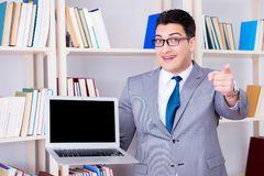 The businessman with a blank screen laptop working in the library. Businessman with a blank screen laptop working in the library Royalty Free Stock Image