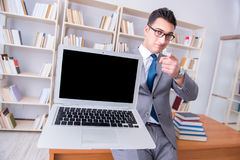 The businessman with a blank screen laptop working in the library. Businessman with a blank screen laptop working in the library Stock Photos