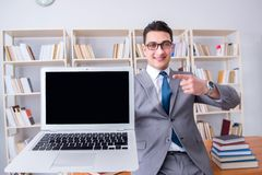 The businessman with a blank screen laptop working in the library. Businessman with a blank screen laptop working in the library Stock Image