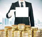 Businessman with blank white paper list in hand and stacks of go Royalty Free Stock Images