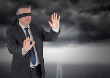 Businessman in blindfold against storm cloud Stock Photo