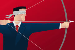 Businessman blindfold hitting target with bow and arrow Royalty Free Stock Photos