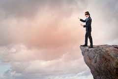 Businessman in blindfold. Image of businessman in blindfold standing on edge of mountain Stock Photo