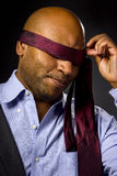 Businessman Blindfolded. Black businessman blindfolded to represent corporate uncertainty and lack of business vision Royalty Free Stock Photo