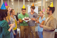 Businessman blowing candles on her birthday cake Stock Image