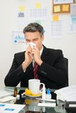 Businessman blowing his nose Stock Photography