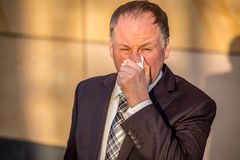 Businessman blowing nose Stock Images
