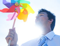 Businessman blowing pinwheel relaxation concept Stock Photography