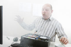 Businessman Blowing Smoke Emerging From Computer Chassis Royalty Free Stock Images