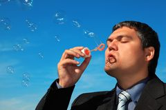 Businessman blows soap bubbles against sky Royalty Free Stock Photography
