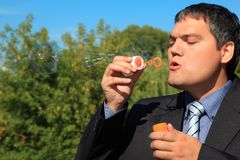 Businessman blows soap bubbles outdoor Stock Photography