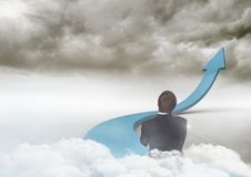 Businessman on blue arrow in the clouds Stock Image