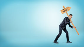 A businessman on blue background holding a heavy road sign with a `Go` writing on it. Stock Photo