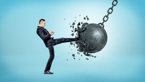 A businessman on blue background kicking at a wrecking ball and crashing it with many pieces flying away. Strength and resolve. Face your troubles. Win against Royalty Free Stock Photos