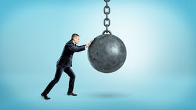 A businessman on blue background pushing at a hanging unmoving wrecking ball. Stock Photo