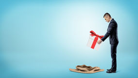A businessman on blue background putting a large gift box into an empty sack. Stock Image