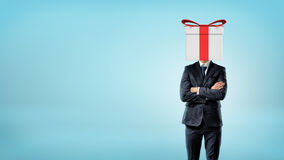 A businessman on blue background standing in front view with his hands crossed and a gift box in place of his head. Royalty Free Stock Images