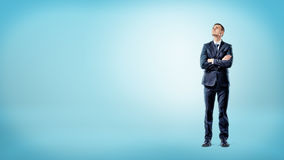 A businessman on blue background standing with hands crossed deep in thought. Royalty Free Stock Photos