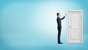 A businessman on blue background touches a white doorframe with a closed door inside. Royalty Free Stock Image