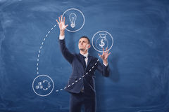 Businessman on blue chalkboard background manipulating white see-through icons that are connected with dash lines. Business and success. Profitable ideas Stock Photo
