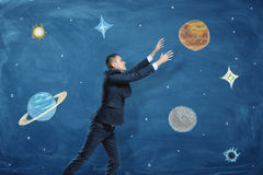 Businessman on blue chalkboard background trying to grasp a drawn planet among many others. Stock Photos