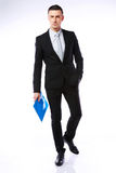 Businessman with blue folder. Studio shot of a businessman with blue folder on gray background royalty free stock photo