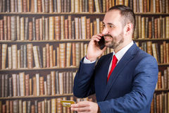 A businessman in a blue jacket and red tie speak to phone with g Stock Photo