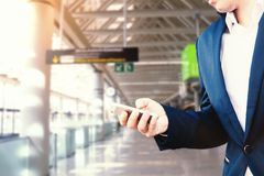 Businessman in a blue jacket and white shirt at the airport holds a smartphone in his hand stock image