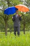 Businessman with blue and orange umbrellas Stock Photos