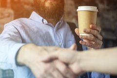 Businessman in a blue shirt drinks coffee and greets the hand with a partner. Coffee business concept royalty free stock photo