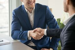 Businessman shaking hand to partner at negotiation. Businessman in blue suit handshaking at business meeting, trying to make positive first impression on partner Stock Photos