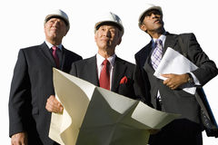 Businessman with blueprint by colleagues, in hardhats, low angle view, cut out Stock Images