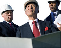 Businessman with blueprint by colleagues, in hardhats, low angle view, cut out royalty free stock image