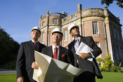 Businessman with blueprint by colleagues, in hardhats, by manor house, low angle view Royalty Free Stock Photography