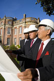 Businessman with blueprint by colleagues, in hardhats, by manor house, low angle view Royalty Free Stock Image