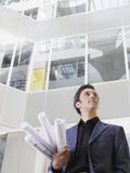 Businessman With Blueprints In Office Royalty Free Stock Photography