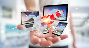 Businessman connecting tech devices and startup rocket 3D render. Businessman on blurred background connecting tech devices and startup rocket 3D rendering Stock Images