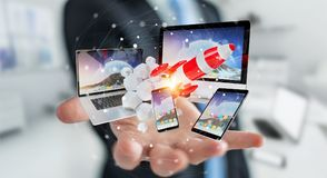 Businessman connecting tech devices and startup rocket 3D render. Businessman on blurred background connecting tech devices and startup rocket 3D rendering Stock Photography