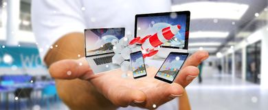 Businessman connecting tech devices and startup rocket 3D render. Businessman on blurred background connecting tech devices and startup rocket 3D rendering Royalty Free Stock Images