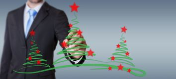 Businessman drawing christmas trees sketch. Businessman on blurred background drawing christmas trees sketch Stock Photography