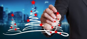 Businessman drawing christmas trees sketch. Businessman on blurred background drawing christmas trees sketch Stock Image