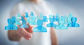 Businessman holding 3D rendering group of blue people. Businessman on blurred background holding 3D rendering group of blue people Royalty Free Stock Image