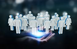 Businessman holding 3D rendering group of people in his hand. Businessman on blurred background holding 3D rendering group of people in his hand Stock Images