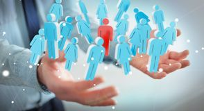 Businessman holding 3D rendering group of people in his hand. Businessman on blurred background holding 3D rendering group of people in his hand Stock Photography