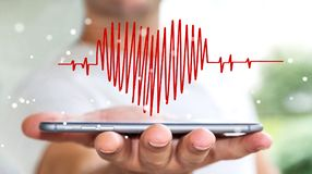 Businessman holding heart beat sketch over mobile phone. Businessman on blurred background holding heart beat sketch over mobile phone Royalty Free Stock Photos