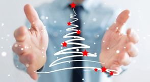 Businessman holding and touching christmas trees sketch. Businessman on blurred background holding and touching christmas trees sketch Royalty Free Stock Photo