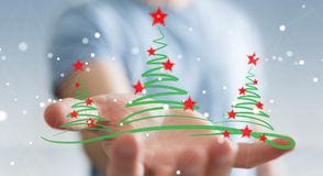 Businessman holding and touching christmas trees sketch. Businessman on blurred background holding and touching christmas trees sketch Stock Image